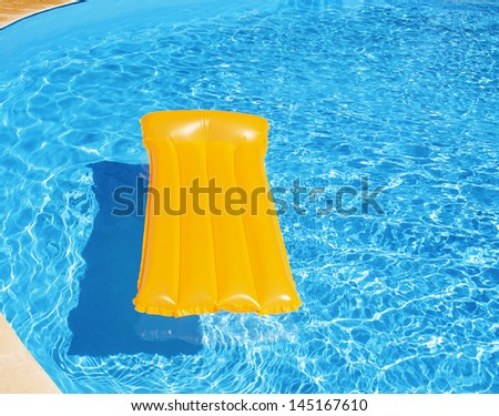 Orange mattress floating in a pool - stock photo