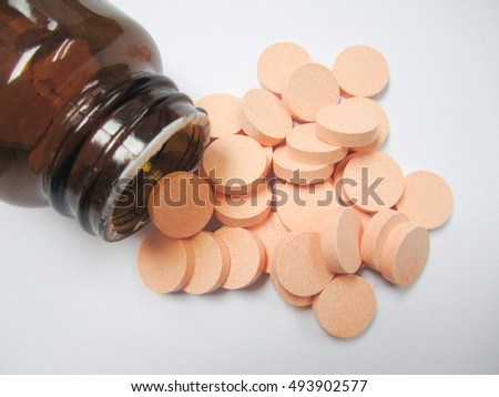 Orange medicines out side from brown bottle on the white background