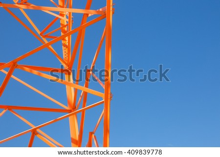 orange metal structures of the tower. part of the high telecommunications tower on background blue sky. copy space for your text