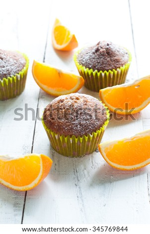 Orange muffins at the white wooden table and sliced oranges - stock photo