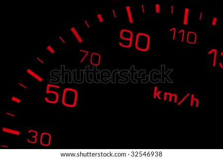 Orange neon speedometer over a black background. Shallow depth of field
