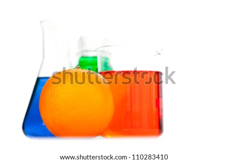 Orange next to beakers against a white background - stock photo