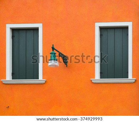 Orange old wall with two windows and a lantern, Burano