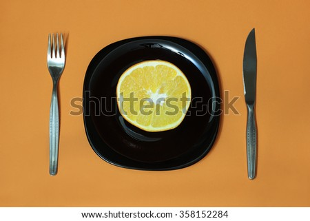 Orange on black glass plate, fork and knife on bright vivid orange background. Top view - stock photo