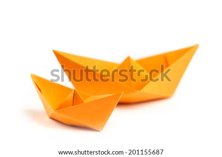 Orange origami paper boats isolated on white