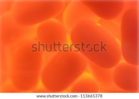 Orange oval particles texture under magnification - stock photo
