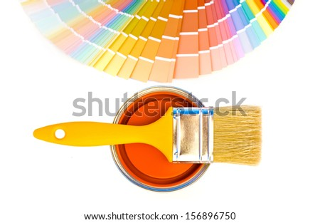 Orange paint and swatch. Samples with different shades of orange and can of orange paint with a yellow brush. Focus on the can. Isolated on white background. - stock photo