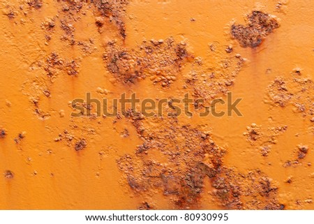 orange painted  hull of a ship with rust coming through