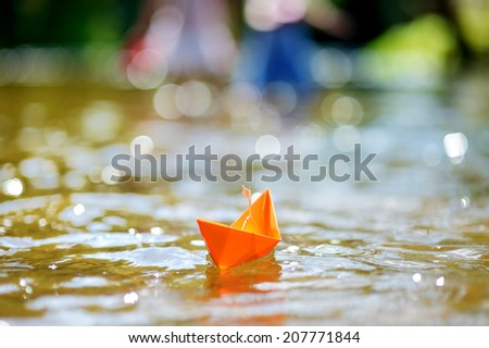 Orange paper boat with a white flag floating on a river - stock photo