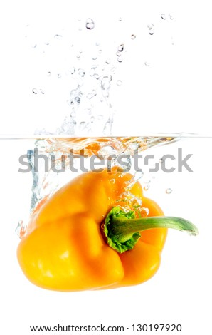 orange paprika pepper splashes into water before white background - stock photo