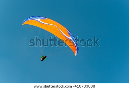 orange paraglider against the blue winter sky - stock photo