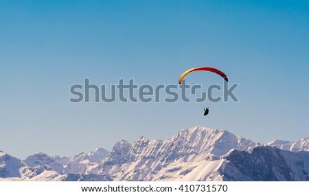 orange paraglider flying through the austrian alps  - stock photo