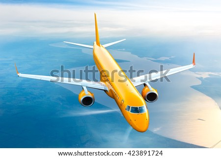 Orange passenger plane is flying in the blue sky over the river - stock photo