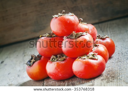 Orange persimmons stacked in a pyramid shape on the old wooden background, selective focus - stock photo