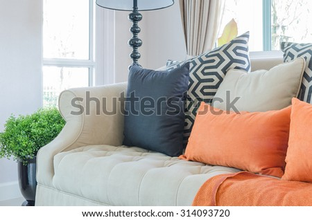 orange pillows and blanket on modern sofa in living room at home - stock photo