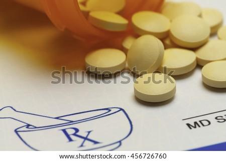 Orange Pills Spilled on RX Medicine Prescription Doctors Note. - stock photo