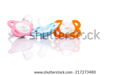 Orange, pink and blue pacifier over white background  - stock photo