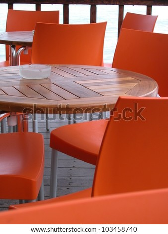 Orange plastic chairs and wooden tables in an outdoor bar - stock photo