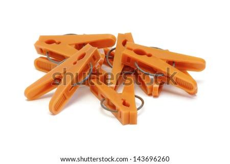 Orange plastic clothespins on white background - stock photo
