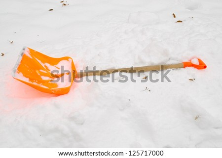 orange plastic snow clean tool lie rest on snowdrift in winter. - stock photo