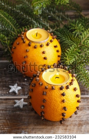 Orange pomander ball with candle, fir branches in the background - stock photo