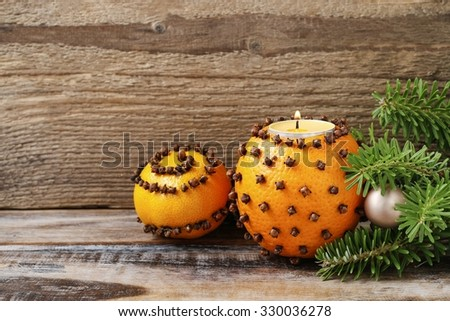 Orange pomander ball with candle on wooden table - stock photo
