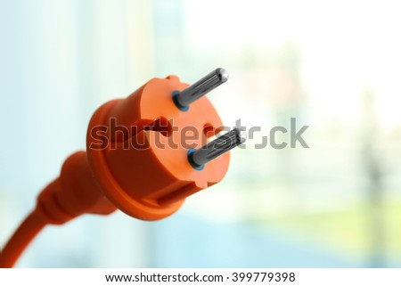 Orange power plug on light blurred background - stock photo