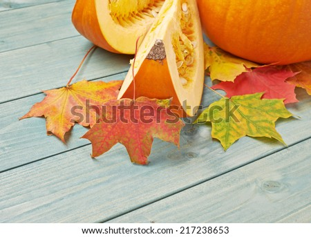 Orange pumpkin and maple leaves composition over the background made of green colored wooden boards