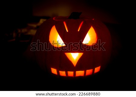 Orange pumpkin with spooky face carved for Halloween isolated on black - stock photo