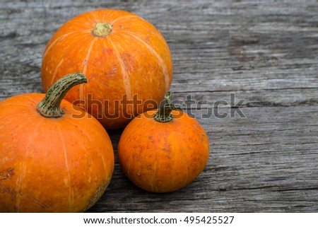 Orange pumpkins on the background of the old grey wooden table