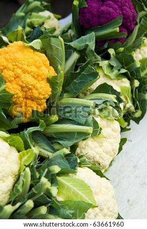 Orange, purple and white cauliflower on display at a farmer's market - stock photo