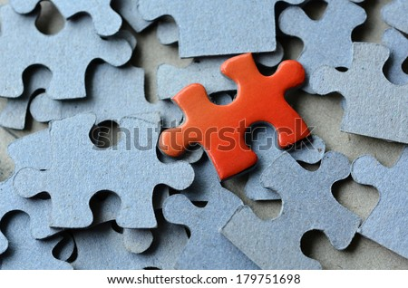 Orange puzzle pice standing above the rest of puzzle pieces. Conceptual photograph to display business, personal, financial success, or a leadership concept. - stock photo