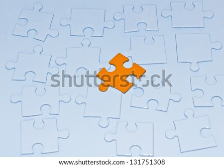 Orange puzzle piece and many white puzzle pieces - stock photo