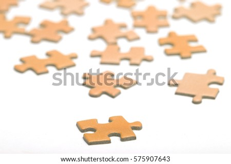 Orange puzzle pieces on a white surface. Focus point on the first piece in front. Abstract and decorative.