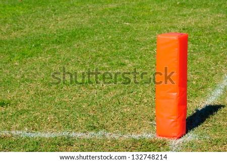 Orange Pylon on a football field. - stock photo