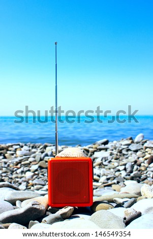 Orange radio set on the beach. - stock photo
