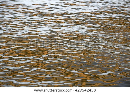 Orange reflection circles on surface water with choppy waves