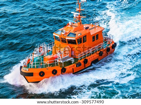 Orange rescue or coast guard patrol boat industrial vessel in blue sea ocean water - stock photo