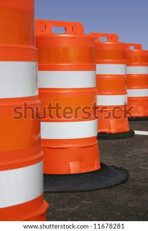 Orange road construction barrels with sharp focus on the second one. - stock photo