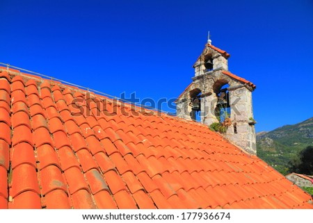 Orange roof tiles and bell tower of orthodox monastery from the Adriatic sea area - stock photo