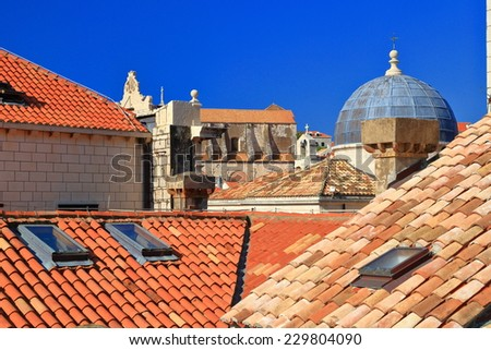Orange roof tops and church dome inside the old town of Dubrovnik, Croatia - stock photo