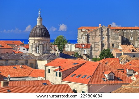 Orange roof tops and tall church dome inside the old town of Dubrovnik, Croatia - stock photo