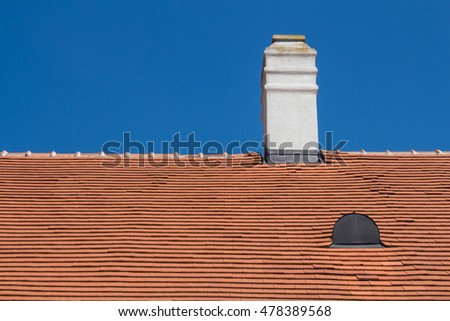 Orange roof with a chimney Old renewed orange roof with a white chimney and a roof window. Bright summer blue sky in the background.