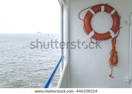 Orange rope with rescue bouy on boat sea n the background - stock photo