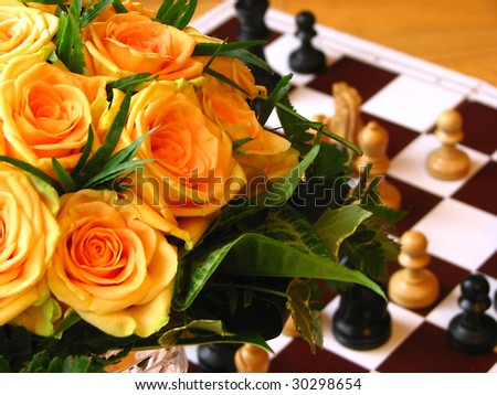 Orange rose with chess figures - stock photo