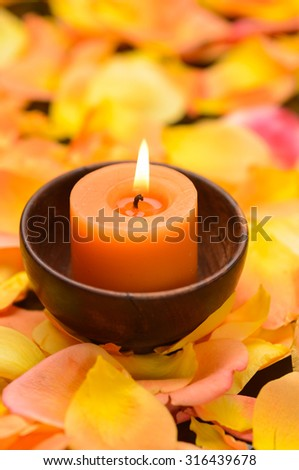 Orange rose with many rose petals with candle  - stock photo