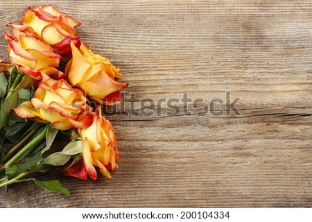 Orange roses on wooden background, copy space - stock photo