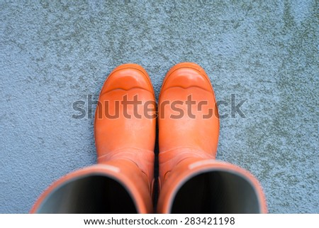 orange rubber boots on a concrete surface with copy space, top view, horizontal - stock photo