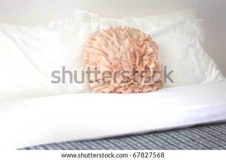 orange ruffled round decorative pillow on bed