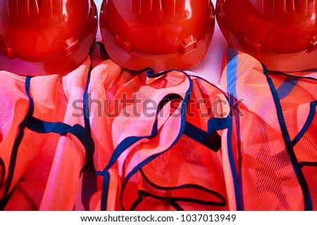 Orange safety vests and orange safety helmets on the hooks on the wall in an industrial placement